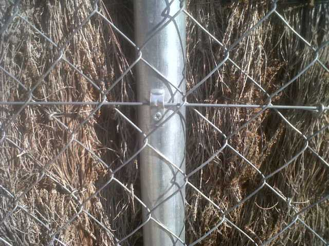Detalle sujeccion de poste con malla metálica y brezo